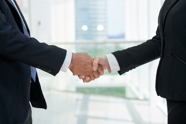 Close-up image of business partners shaking hands at meeting